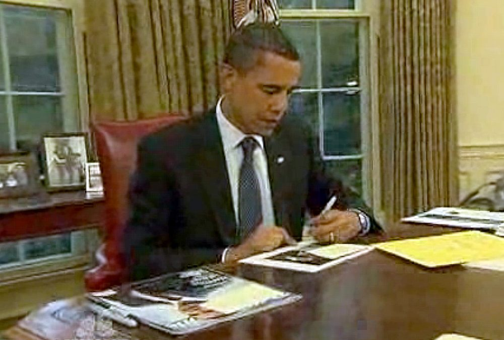 President Obama working at his desk in the Oval Office